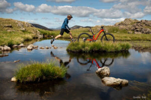Mann springt über Wasser zu einem Mountainbike